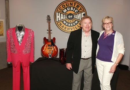 Country Music Hall of Fame member Roy Clark donated several items to the Country Music Hall on Fame® and Museum on Saturday (7/18).  The artifacts, which will be on display beginning August 1 in the Museum's permanent exhibit, include a magenta three-piece Manuel suit with an embroidered silver lame` Manuel shirt, patent leather Tony Lama boots, and a Heritage H-535 Roy Clark Signature model electric guitar.  Pictured—Clark and Vice President of Museum Services Carolyn Tate  Photo by Richard Suter