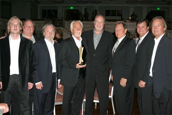 Kenny Rogers celebrates after receiving the Cliffie Stone Pioneer Award. (L-R)Dreamcatcher's Jason Henke, Webster PR's Kirt Webster, Dreamcatcher's Bob Burwell, Kenny Rogers, Capitol Records Mike Dungan, Dreamcatcher's Jim Mazza, lawyer Bruce Phillips, and Dreamcatcher's Kelly Junkerman.