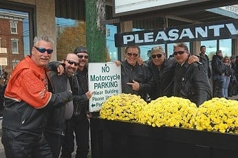 """Left to right, Steve Pugliese, Jeff Hill, Rich Bredbenner, Pat Garrett, Joe  Dell, and Bob Stevenson have a laugh at the sign outside The Bridge Inn in Pleasantville where dozens of  motorcycles were parked, with permission by owners, during the taping of Garrett's new video """"Wild Hog""""."""