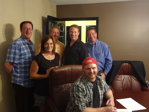 Pictured (L-R) are: Sam Ramage, Chief Creative Officer, Blue Guitar; Lori Maxwell, CFO, Blue Guitar; Danny Pool, owner of the publishing company; Mike Kraski, General Manager, Blue Guitar; Daniel Wood, President, Blue Guitar and Timmer (seated).