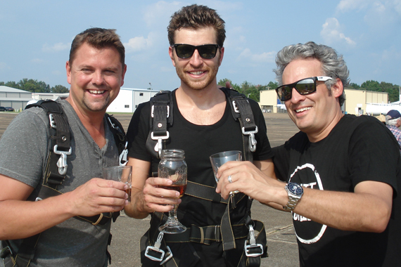 """Atlantic/WMN recording artist Brett Eldredge recently made good on his promise to skydive if his single """"Don't Ya"""" made it to the top of the charts. Pictured (L-R): Storme Warren (SiriusXM), Eldredge, and Byron Kennedy (KNCI)"""
