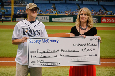 Scotty McCreery presents a $5,000 donation to Suzanne Luecke, Rays Baseball Foundation