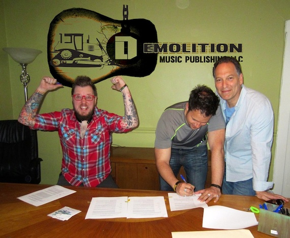 Pictured, (L-R): Adam Searan and Jason Eustice sign contracts on the first official day of business for Demolition Music Publishing, Nashville, during a meeting with songwriter Jon D'Agostino, the firm's president and CEO.