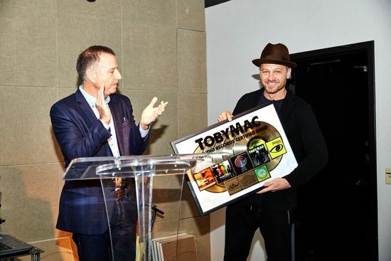 Capitol Christian Music Group President & CEO Bill Hearn presents TobyMac with a plaque to commemorate five studio records RIAA Certified Gold