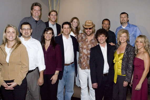 An August 31, 2005 press conference where Scott Borchetta and Toby Keith announced two business entities equally share the same staffing resources—Keith's Show Dog and Borchetta's Big Machine. Pictured (L-R): Front: Darcy Miller-Lashinsky (Secondary Promotion/Promotion Coordinator), Tony Morreale (Southeast Promotion & Marketing), Lisa Owen (West Coast Promotion & Marketing), Zach Horowitz (President and Chief Operating Officer of Universal Music Group), Toby Keith, Scott Borchetta (President - Big Machine Records), Denise Roberts (VP/Promotions) , Sandi Spika-Borchetta (Creative Services); Back: Greg Sax (Southwest Promotion & Marketing), John Zarling (National Promotions & New Media), Suzanne Durham (Northeast Promotion & Marketing), George Nunes (GM/Show Dog), Andrew Kautz (Controller/Office Manager)