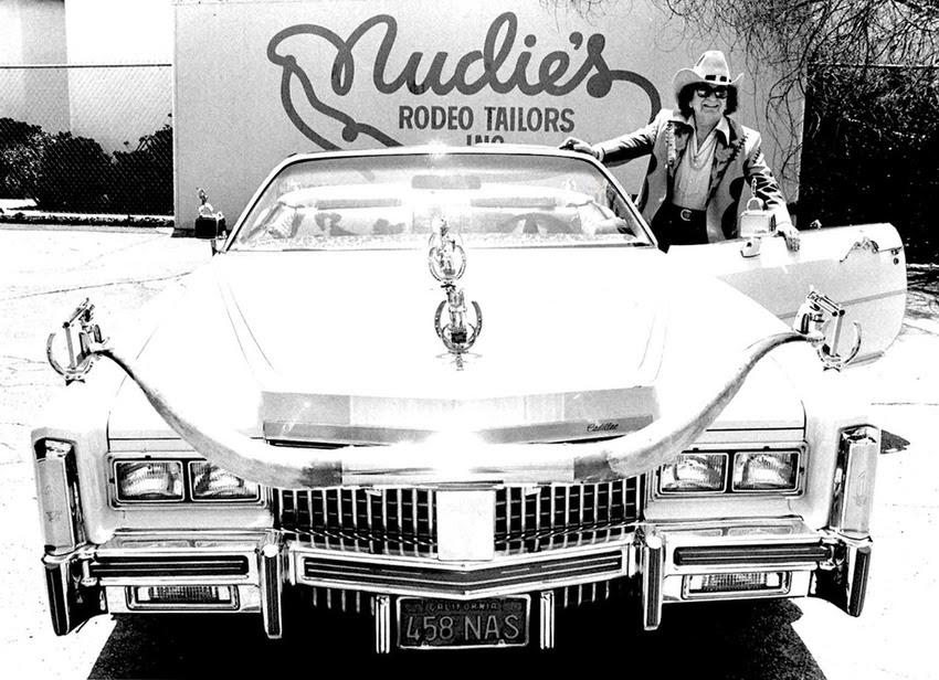 """Cohn was equally famous for his garishly decorated automobiles. Between 1950 and 1975 he customized 18 vehicles, mostly white Pontiac Bonneville convertibles, with silver-dollar-studded dashboards, pistol door handles and gearshifts, extended rear bumpers, and enormous longhorn steer horn hood ornaments. Pictured here: Nudie with one his classic decorated 'Nudie Mobiles"""""""