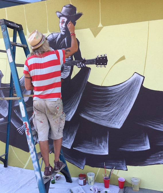 Mike Shine paints a mural on the side of Carnival Music.