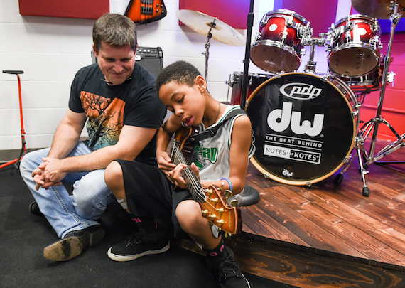 A local music student strums a few chords for hit songwriter Rob Hatch during the Notes for Notes grand opening Tuesday in New Orleans. Photo: Erika Goldring / CMA