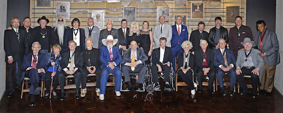 """Standing (L-R): Duane Allen, Garth Brooks, Bobby Bare, William Lee Golden, Richard Sterban, Joe Bonsall, Curtis Young, Steve Turner, Dolly Parton, CMA Chief Executive Officer Sarah Trahern, CMA Board Chairman John Esposito, Country Music Hall of Fame and Museum Director Kyle Young, Jeff Cook, Teddy Gentry, Vince Gill, and Charley Pride. Seated (L-R): Ralph Emery, Jo Walker Meador, Harold Bradley, Kris Kristofferson, Charlie Daniels, Fred Foster, Randy Travis, Brenda Lee, Charlie McCoy, E.W. """"Bud"""" Wendell, and Roy Clark."""
